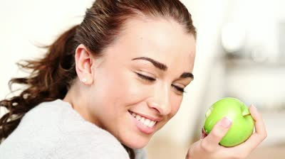 stock-footage-healthy-young-woman-eating-green-apple-and-smiling-at-home-indoors